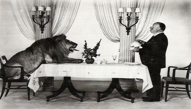 Alfred Hitchcock and the MGM Lion Leo having tea together.